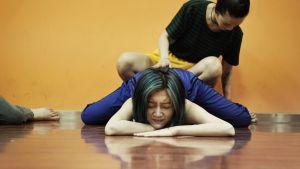 nainen makaa lattialla venytysasennossa, hänen takanaan on toinen nainen
