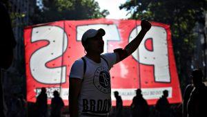 Mielenosoittaja kuvattu punavalkoista lakanaa vasten.