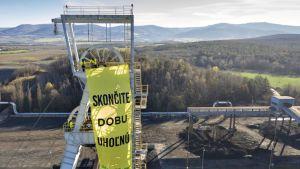 Kuva tehtaan tornista, jossa heiluu keltavihreä Greenpeacen lippu.
