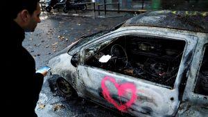 Mies katselee pahoin palanutta autoa Pariisissa sunnuntaiaamuna 2. joulukuuta. Ovessa on spray-maalilla maalattu pinkinpunainen sydän.