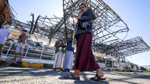 Jemeniläiset kävelevät  ilmaiskun tuhoaman rakennuksen ohi.