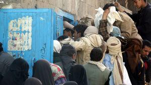 Ihmiset jonottavat leipää hyväntekeväisyysleipomon edessä Jemenin pääkaupungissa.