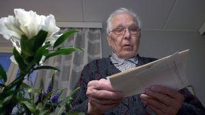 Olavi Koivisto lukee saamaansa kutsua Linnan juhliin