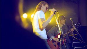 Laulaja nojaa mikrofonitelineeseen ja nuori mies soittaa taustalla akustista kitaraa