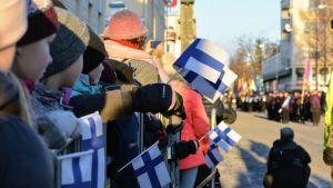 Kuva väkijoukosta katsomassa paraatia käsissään suomenlippuja.