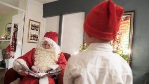 Joulupukki jakaa joululahjoja perheen kotona.
