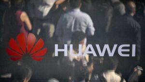 Huawein logo, taustalla ihmisiä