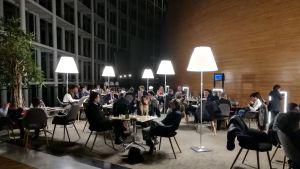 EU-parlamentin henkilöstö istuu pöydissä parlamenttirakennuksen sisällä.