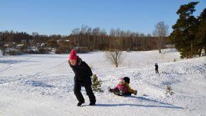 Pulkkailijoita lumisessa maisemassa.