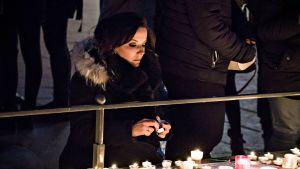 Nuori nainen sytyttämässä kynttilää Strasbourgin keskusaukiolla keskiviikkona 12. joulukuuta.