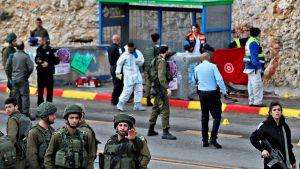Israelilaisia sotilaita ja rikosteknikkoja bussipysäkin läheisyydessä 13. joulukuuta.