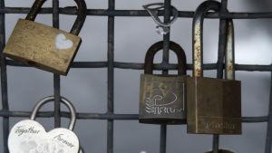 Lähikuvassa kolme rakkauslukkoa, jotka on kiinnitetty Tammerkosken ylittävän kävelysillan kaiteeseen Tampereella