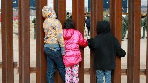 Kolme lasta katselee metallisten tankojen läpi, toisella puolella vihreä asuisia miehiä.