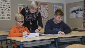 Opettaja opastaa oppilaita koulussa.