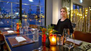 Hanna Lintumäki istuu Kitchen & Table -ravintolan pöydässä.