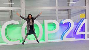 Nainen poseeraa COP24-kyltin edessä.