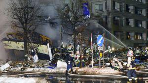 Palomiehet sammuttavat ja raivaavat räjähdyspaikkaa.