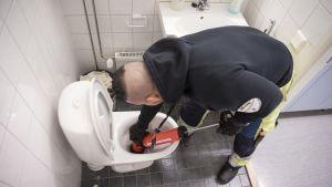 Putkimies avaa tukkeutunutta vessanpönttöä.
