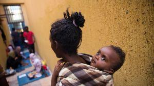 Äiti lapsi selässään kapealla käytävällä