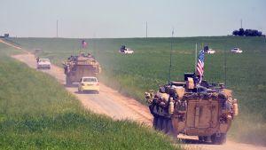 Hiekkatiellä autoja sekä tankkeja, joissa Yhdysvaltain lippuja
