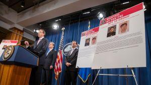 Yhdysvaltain pääsyyttäjä Rod Rosenstein (vas.) ja FBI:n johtaja Christopher Wray (kesk.) tiedotustilaisuudessa Washingtonissa. Kuvassa olevia kiinalaismiehiä vastaan on nostettu syytteet vakoilusta.