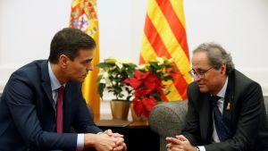 Kaksi miestä istuu vastakkain, taustalla punakeltaiset liput.