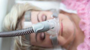 CPAP ylipainehengityslaiteen maski naisen kasvoilla.