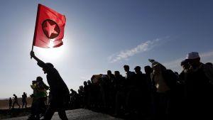 Kurdien työväenlippua liehutetaan kurditaistelijan hautajaisaattueessa.