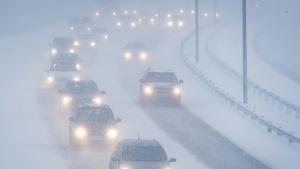 Autoja ajaa lumisateessa