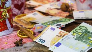 Rahaa ja joulukoristeita pöydällä.