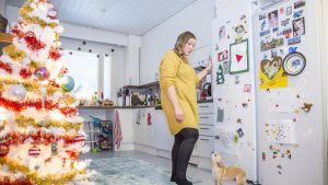 Nainen seisoo keittiössä ja puhuu koiralle.