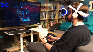 Kuvassa mies pelaa VR-lasit päässä peliä