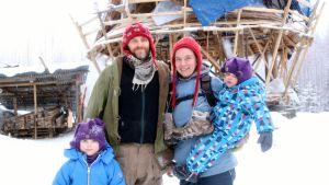 Nelihenkinen lapsiperhe rakenteilla olevan talonsa edessä.