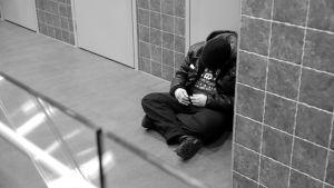 Mies nukkuu kauppakeskuksen käytävässä.
