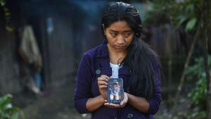 Kuolleen pojan sisko Catarina Gomez Lucas pitelee puhelinta, jossa on kuva hänen veljestään Felipe Gomezista Yalambojochin kylässä, Guatemalassa 28. joulukuuta.