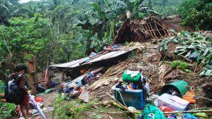 Nainen tutki myrskyssä vaurioitunutta taloaan.