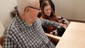 Karva-Kaveri -koira tapaamassa ikäihmisiä hoivakodissa.