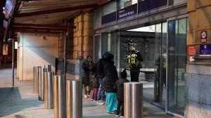 Ihmisiä Manchester Victoria -aseman ulkopuolella.