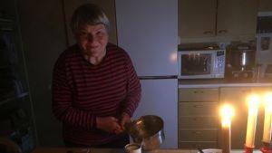 Raija Vehmala laittaa aamupalaa kynntilänvalossa. Kädessään hänellä on kattila ja pöydällä voileipätarvikkeita.