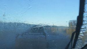 Aallot mereltä iskeytyvät henkilöauton tuulilasiin, kun se on lossin kyydissä.