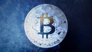 Kuvassa on tummalla taustalla jäätynyt huurteinen bitcoin - kolikko