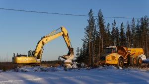 Kaksi työmaakonetta – kaivuri ja jumpperi – talvimaisemassa KymiRingin moottoriratatyömaalla.