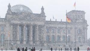 Ihmisiä kulkee lumisateessa Valtiopäivätalon edessä eilen Berliinissä.