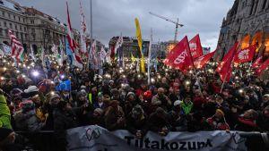 Mielenosoittajajoukko seisoo rakennusten ympäröimällä aukiolla pimenevässä illassa.