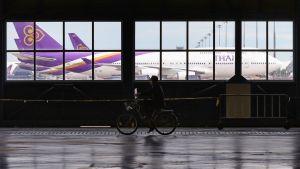 Thaimaalainen vartija polkee pyörällä lentokentällä