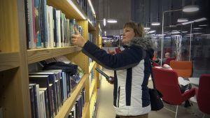 Viveca Särkelä tutkii kirjoja Apila kirjastossa
