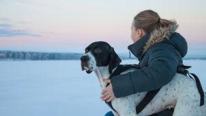 Tyttö ja koira joen rannassa