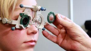 Optikko tarkistaa nuoren näköä.