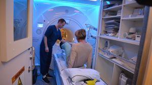 Röntgenhoitaja Touko Vahtera avustaa Minna Näreharjua, jonka polvea kuvataan.