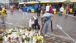 Ihmiset toivat kynttilöitä puukkoiskun uhrien muistolle Turun kauppatorille 19. elokuuta 2017.